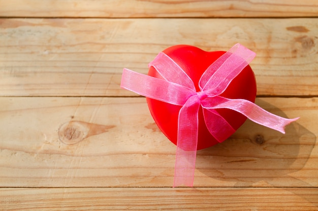 A red heart with bow on plank