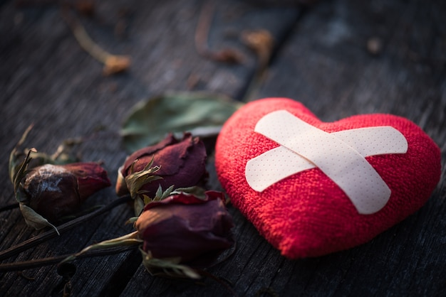 Red heart with dried red rose on wooden background.