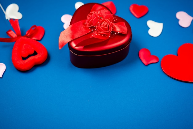 Red heart with a gift to valentine's day on a beautiful blue background. heart pendant.
