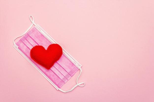 Красное сердце с медицинской защитной маской на светло-розовом фоне, вид сверху, копия пространства. концепция здравоохранения, самообороны