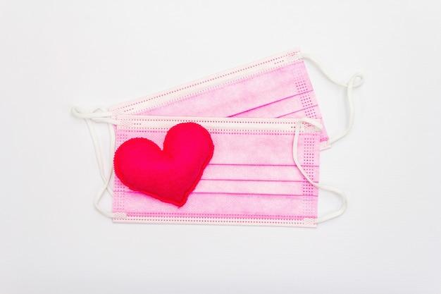 Красное сердце с масками медицинской защиты, изолированные на белом фоне, вид сверху, копией пространства. концепция здравоохранения, самообороны, плоская планировка