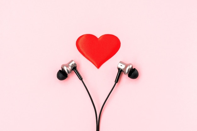 Red heart with pair of black music earphones