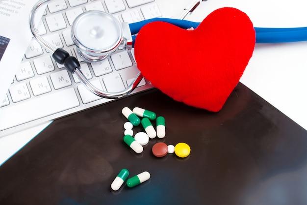 薬、錠剤、カプセル、聴診器、キーボードと赤いハート