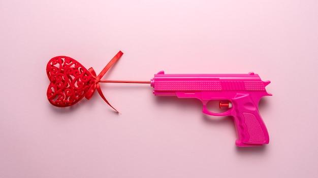 분홍색 파스텔 배경에 분홍색 총을 든 붉은 심장