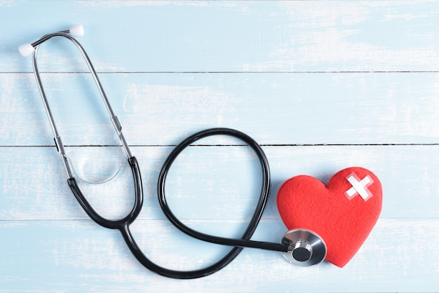 Red heart with stethoscope on blue and white pastel wooden background.
