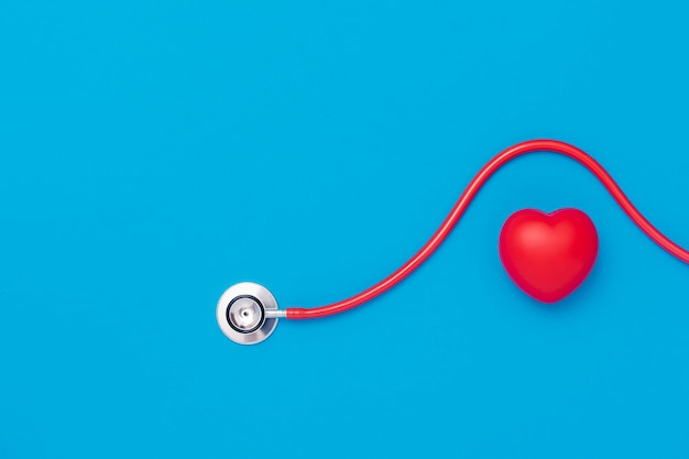 Red heart with stethoscope on blue