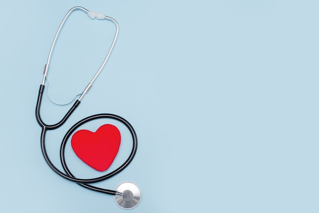 Красное сердце со стетоскопом на синем фоне. скопируйте пространство. день святого валентина.