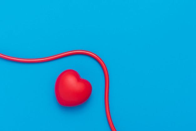Красное сердце со стетоскопом на синем