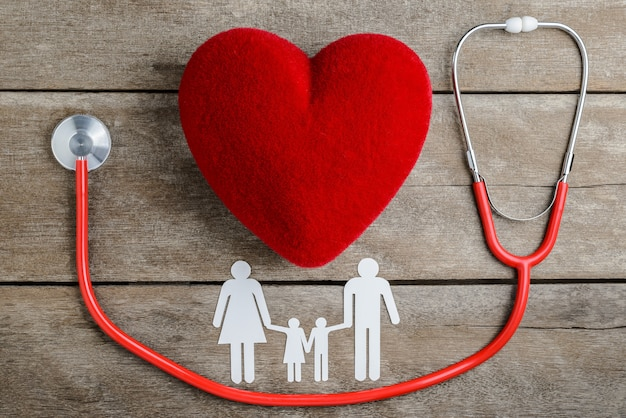 Red heart with stethoscope and paper chain family on wooden table