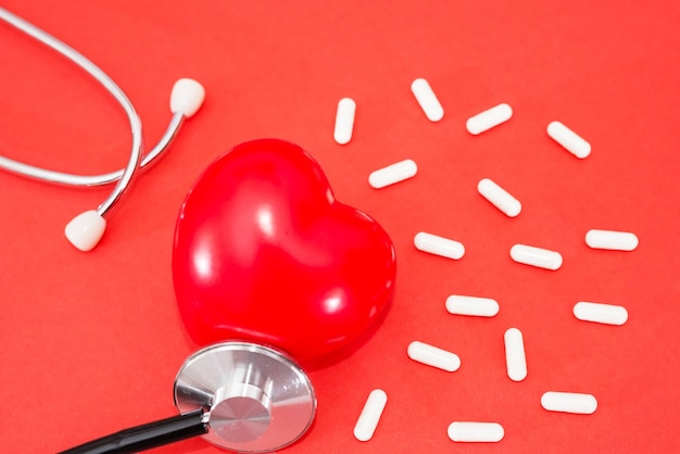 Red heart with a stethoscope and pills, on a red background. healthy heart concept.