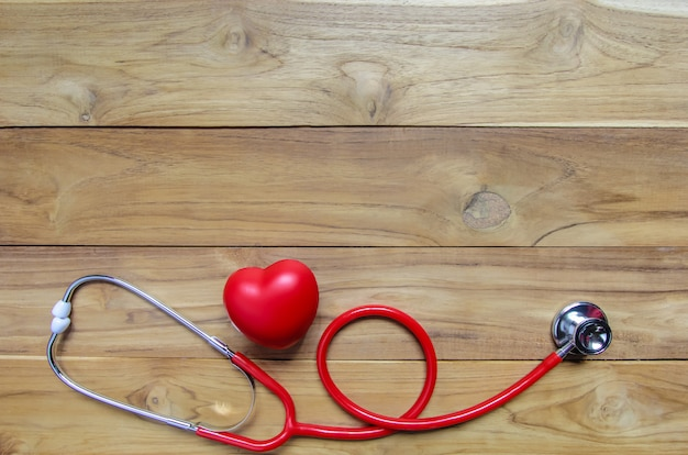 Red heart with stethoscope on wooden background. copyspace. cardiology.