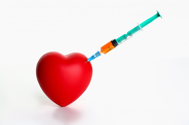 Red heart with stuck syringe on gray background