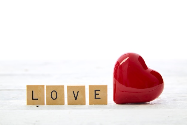 Red heart with valentines day text love wooden letter blocks on white table