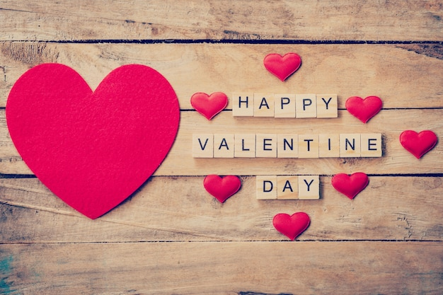 Red heart with wooden text happy valentine day on wood table background.