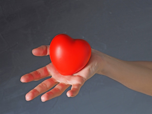 Red heart in a woman's hand on a dark background. the concept of charity. helping loved ones