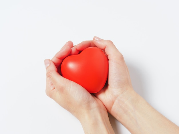 Red heart in women's hands isolated on a white background. concept of charity, health, and love