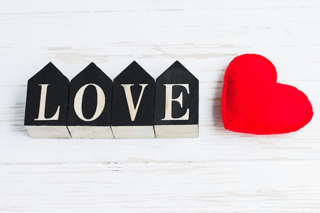 Red heart and wooden figures with the inscription love on a white wooden background. happy valentine's day