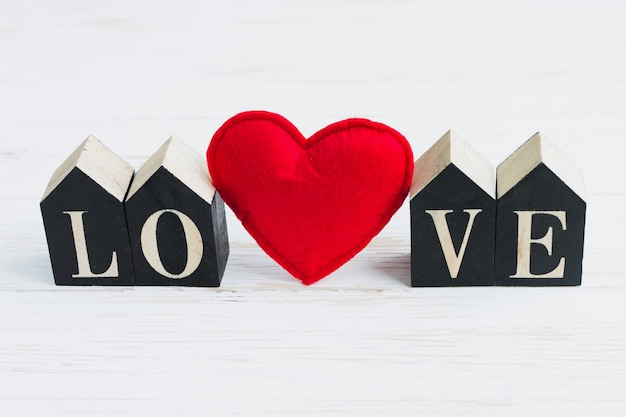 Red heart and wooden figures with the inscription love on a white wooden background