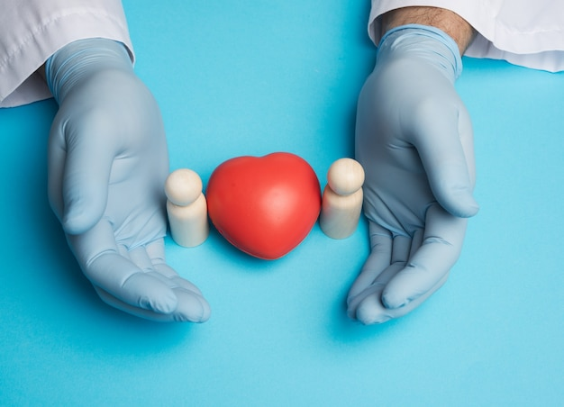 Red heart and wooden figurines of a family, doctor's hands in blue gloves, top view