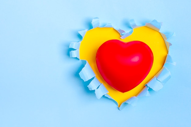 Red heart on yellow heart shape hole through blue paper flat lay
