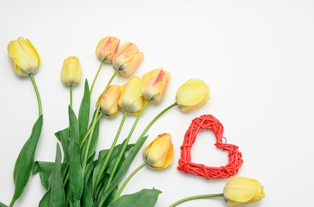 Red heart and yellow tulips on white surface, top view, valentine's day surface