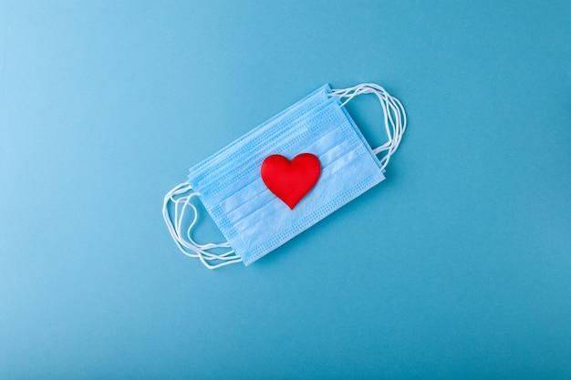 赤いハートと抗エピデミックブルーの医療用保護マスク、コンセプトバレンタインデー、愛、健康へのケア、医師のおかげで、コピースペース、水平、上面図、フラットレイ
