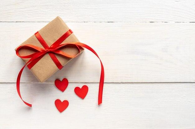 Красные сердца и подарочная коробка корабля на белом деревянном столе. концепция дня святого валентина. плоская планировка, вид сверху.