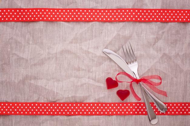 Красные сердечки и столовые приборы на холщовой скатерти