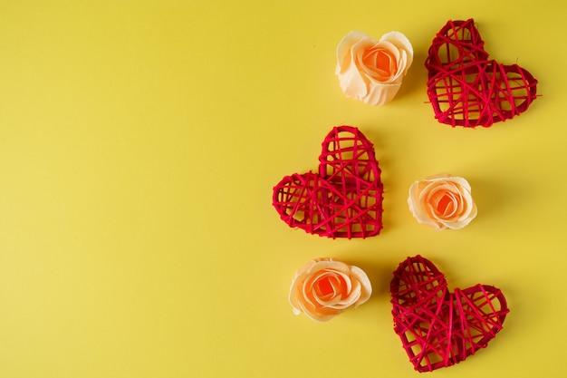 黄色の背景に赤いハートと花、バレンタインデーのデザインはがき。あなたのテキストのための場所。