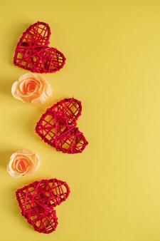 黄色の背景に赤いハートと花。バレンタインデーのグリーティングカードのデザイン