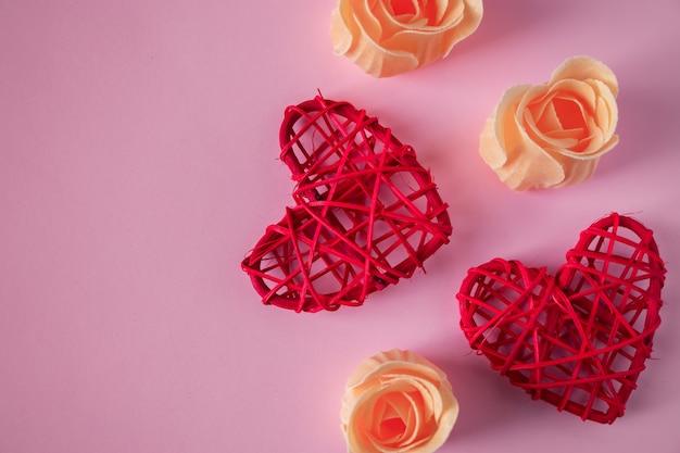 ピンクの背景に赤いハートとオレンジ色のバラのつぼみ。バレンタインデーのコンセプト。テキストの場所。