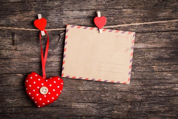 Красные сердца и бумажная карточка, висящая на веревке красными зажимами на деревенском фоне