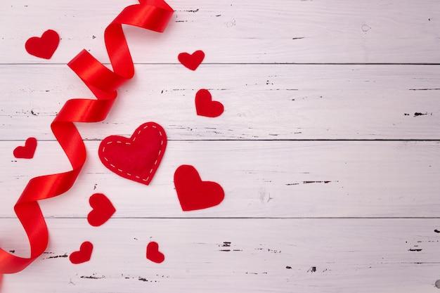 白い木製の背景に赤いハートとリボン。上面図、テキスト用の空き領域。バレンタインデー、愛。