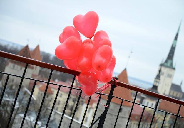 에스토니아의 발렌타인 데이 러브 스토리를 위한 유럽 탈린 구시가지의 탁 트인 전망 뒤에 있는 레드 하트 풍선. 여행 개념입니다. 놀라운