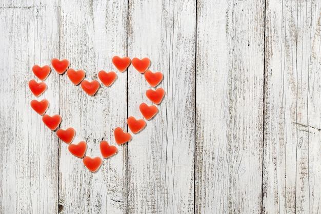 흰색 나무 바탕에 큰 마음을 형성하는 빨간 하트 사탕. 발렌타인 데이에 대한 개념입니다.