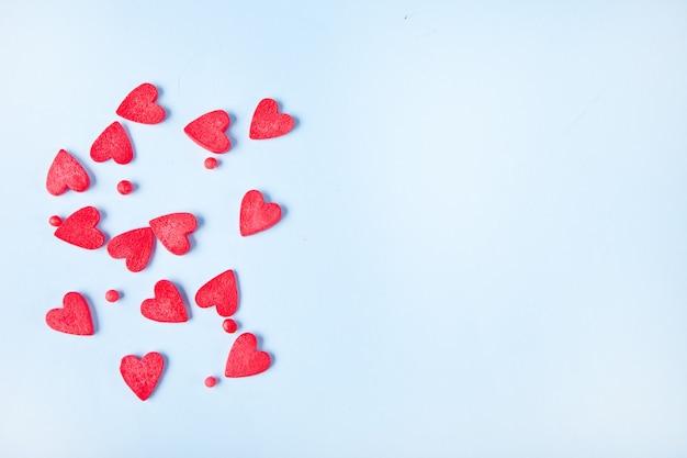 Красные сердца конфеты сахар на светло-синем фоне. концепция дня святого валентина. вид сверху. скопируйте пространство.