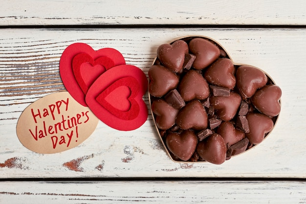 Red hearts and chocolates. greeting paper aside of candies. simple sweet greeting.