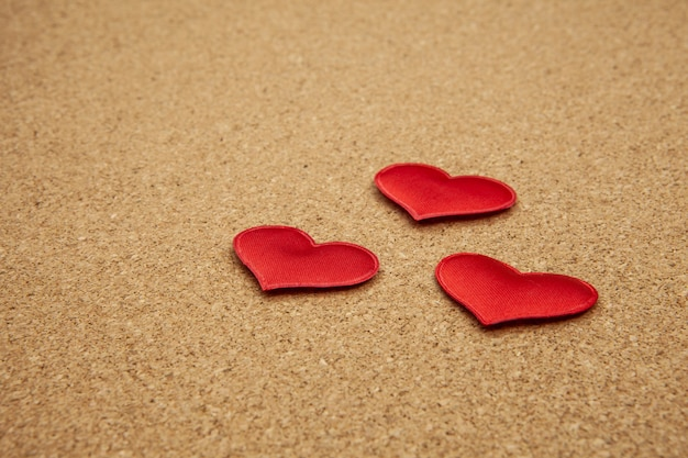 Red hearts on corkboard, strong love concept