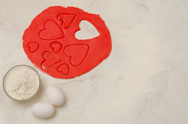 Red hearts cut out dough with eggs and flour on a white table, with space for text, close-up