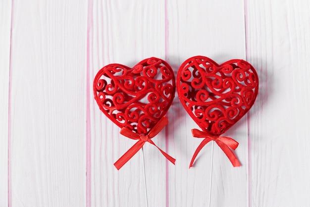 結婚式の休日と2月の聖バレンタインのための木製の背景にパターンの赤いハートの装飾