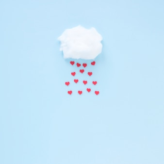 Red hearts falling from cloud