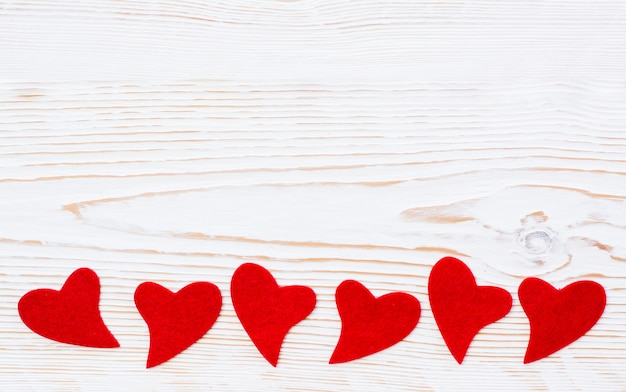 Red hearts of felt on a white wooden
