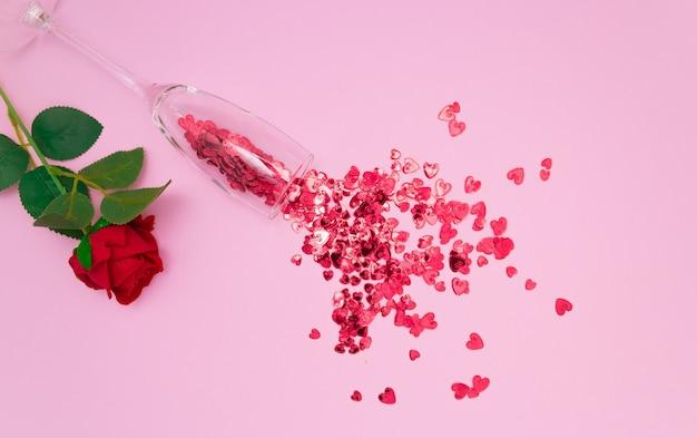 Красные сердца текут из бокала шампанского и розы
