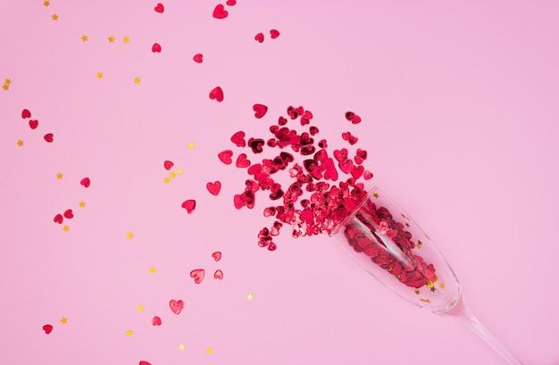 Красные сердца текут из бокала с шампанским