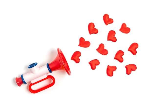 Red hearts fly out of the children's toy pipe on white.