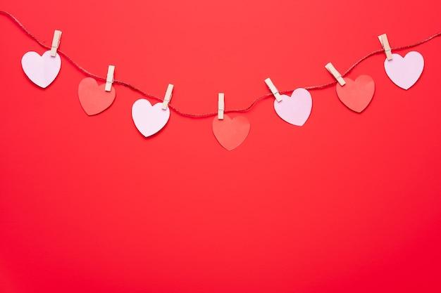Гирлянда из красных сердечек висит на стене