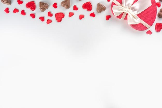 Красные сердечки, подарок с лентой и шоколадными сердечками, день святого валентина