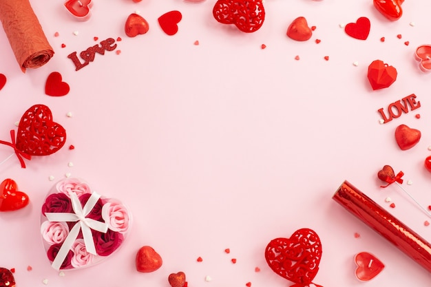 Красные сердечки, подарки и свечи на праздничном розовом.