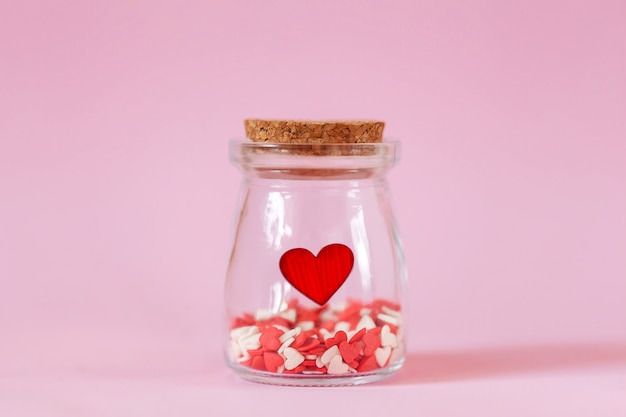 Red hearts in a glass jar on pink wall.