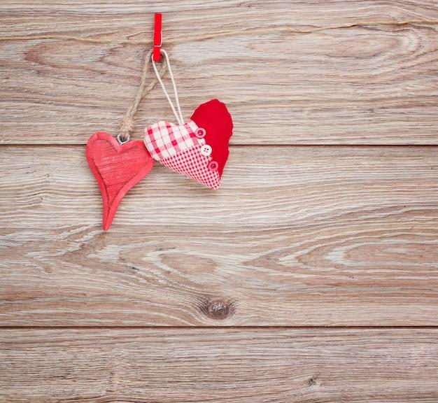 木製の背景にロープにぶら下がって赤いハート